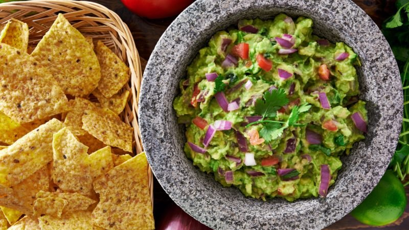 mexican guacamole in molcajete with tortilla chips