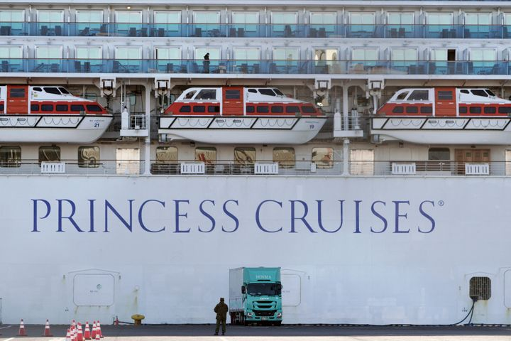 A passenger stands on the balcony of the quarantined cruise ship Diamond Princess on Sunday, Feb. 9.