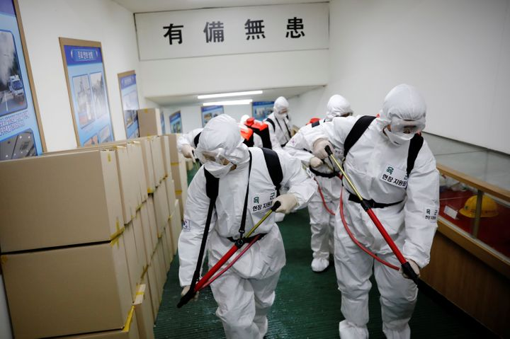 South Korean soldiers wearing protective gear sanitize inside the facility of a city hall after the rapid rise in confirmed c
