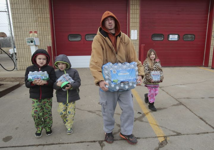 Flint resident Jerry Adkisson and his children carry water bottles from a fire station.