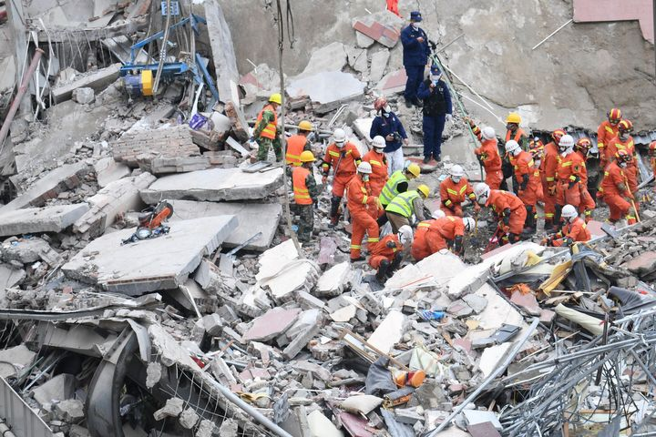 In this photo released by Xinhua News Agency, rescuers search for victims at the site of a hotel collapse in Quanzhou, southe