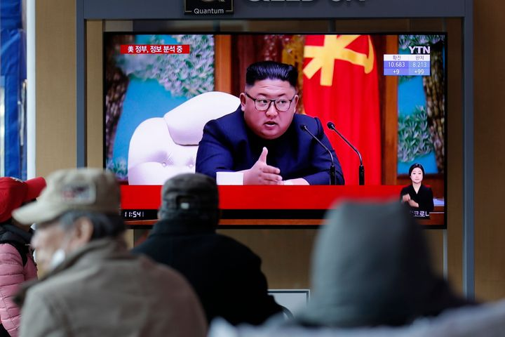 People watch a TV screen showing a news program reporting about North Korean leader Kim Jong Un with a file image at the Seou