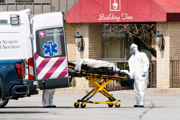 Medical workers load a deceased body into an ambulance outside a New Jersey nursing home.