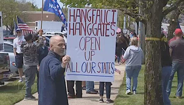 Protester holds threatening sign at Long Island protest against COVID-19 safety precautions.