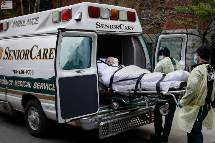 FILE - In this April 17, 2020, file photo, a patient is loaded into an ambulance by emergency medical workers outside Cobble