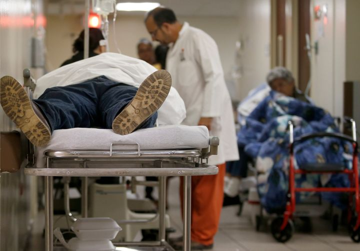 A patient lies in a hospital bed in the hallway inside the emergency room at the Grupo HIMA San Pablo hospital in Caguas, Pue