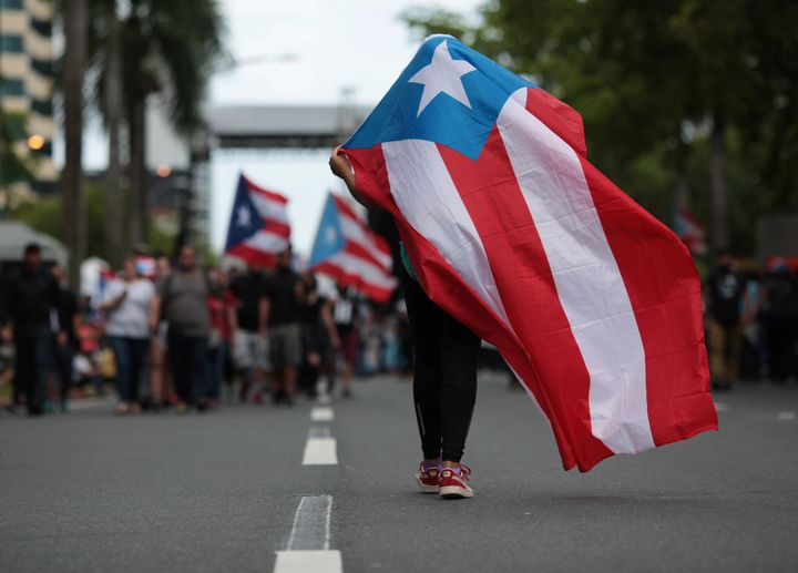 A person carries a Puerto Rican national flag during a protest against the government's austerity measures in 2017.&nbs