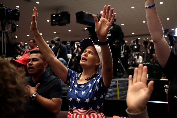 Wanda Albritton of Miami Springs, Florida, raises her arms in prayer at a rally for evangelical supporters at the King Jesus