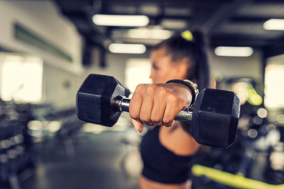 Avoid gym injury woman in gym lifting weights