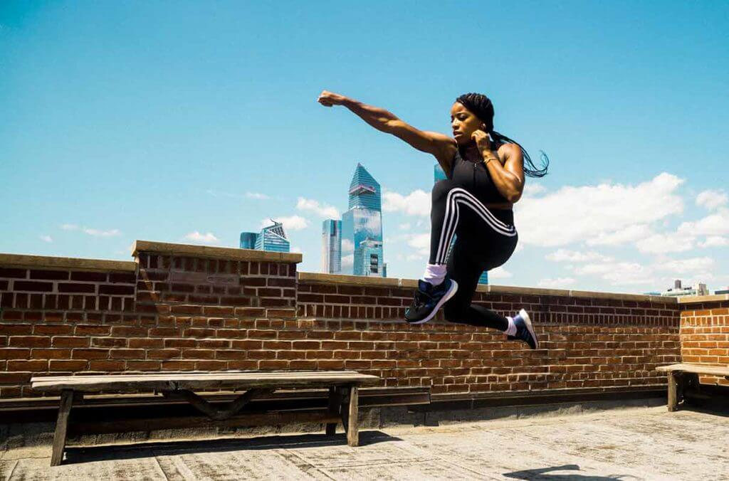 Woman is training on top of a building to grow muscles