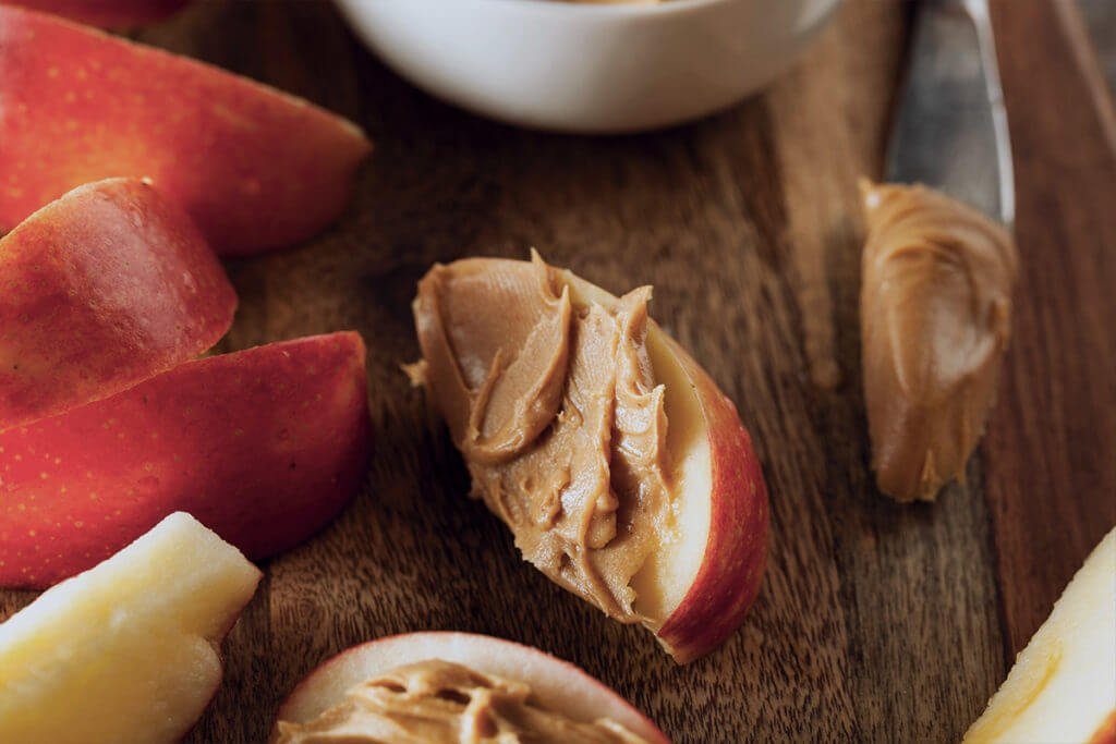 Healthy snack for Nighttime weight loss: a crisp slice of apple and a scoop of creamy peanut butter, ready to be devoured!