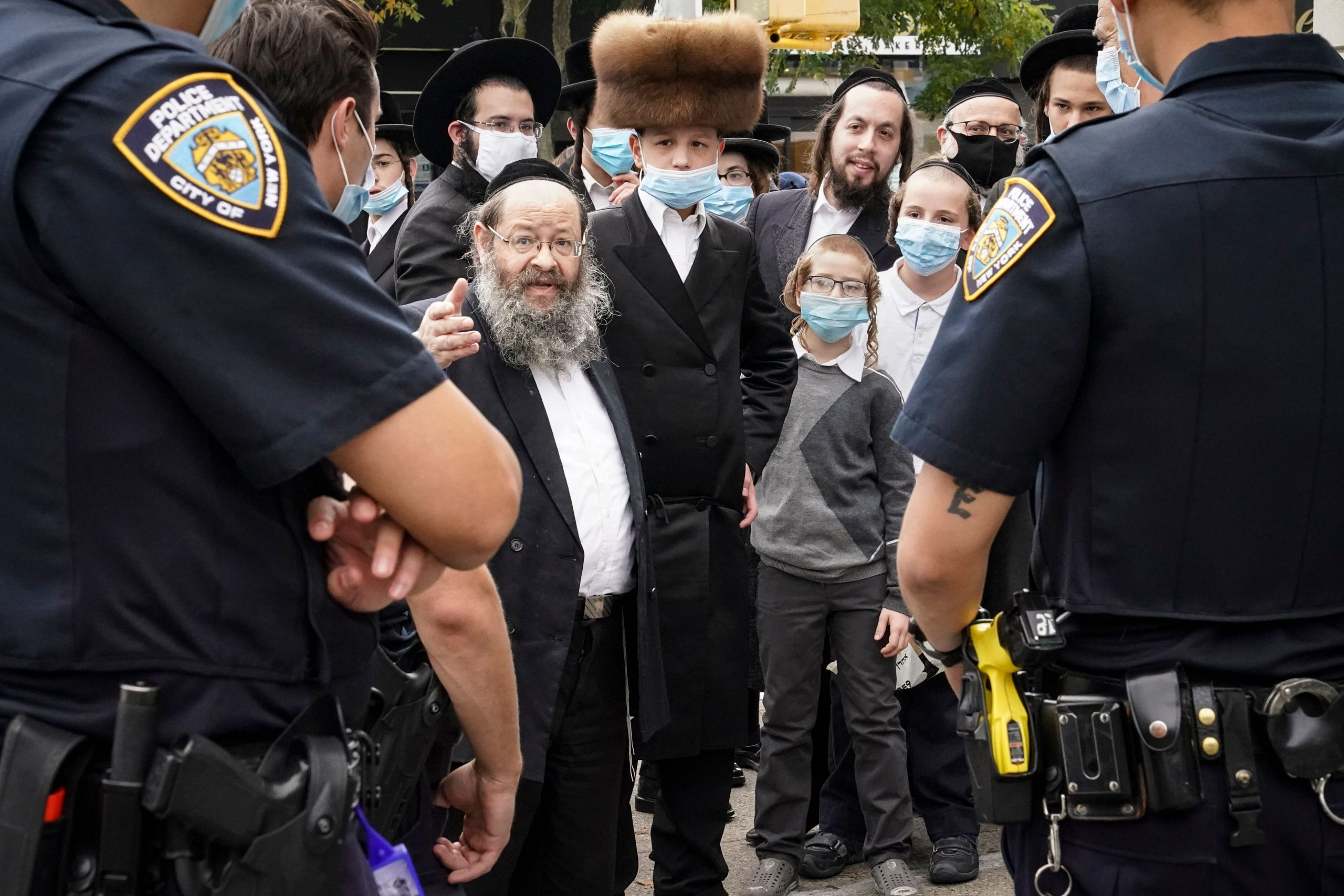 Members of the Orthodox Jewish community speak with NYPD officers on a street corner in the Borough Park neighborhood of Broo