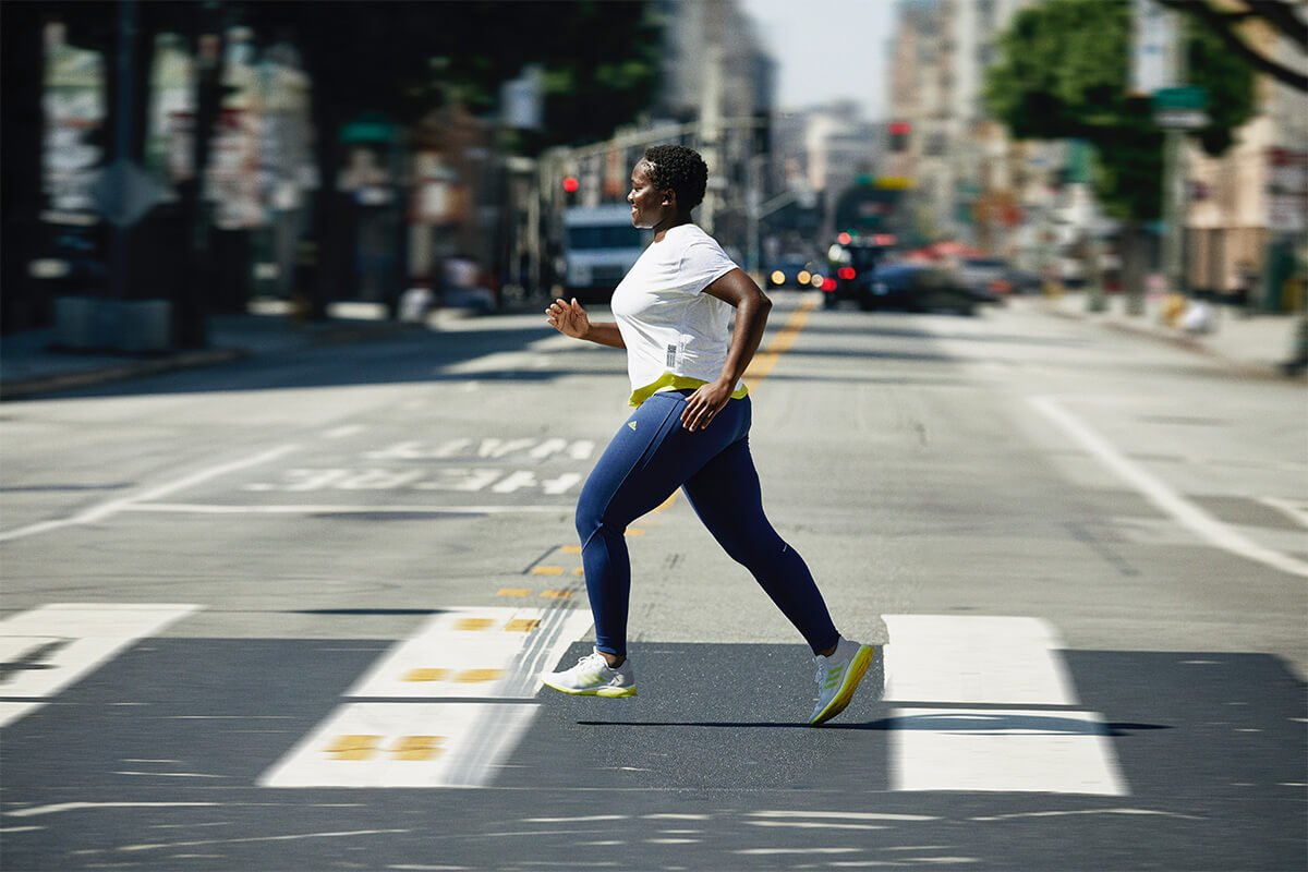 Female running in city with adidas shoes