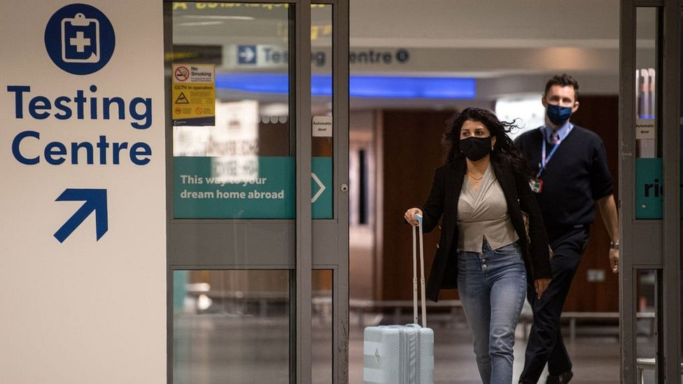 woman with bags at airport wearing mask by testing centre sign