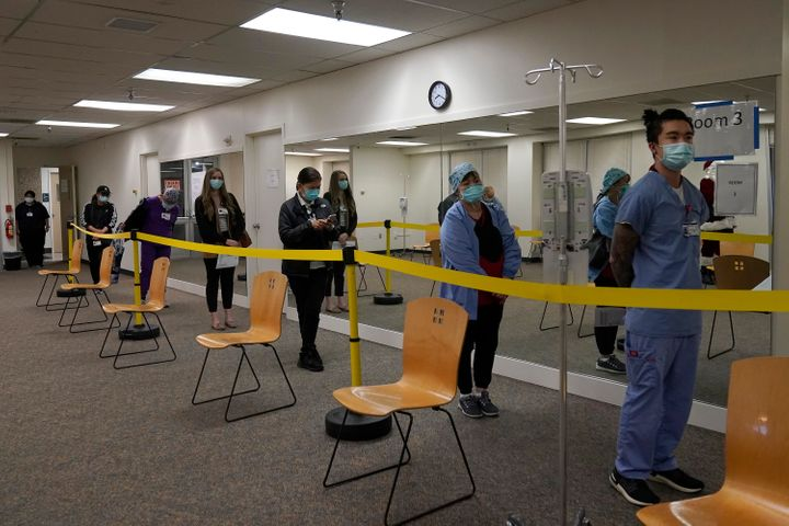 Healthcare workers wait in line to receive the Pfizer-BioNTech COVID-19 vaccine at Seton Medical Center in Daly City, Calif.