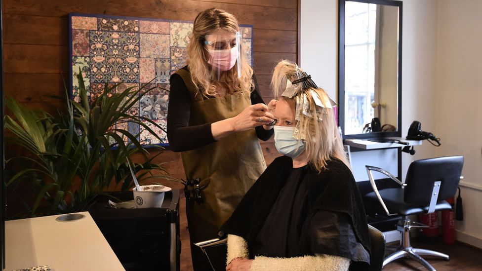 Amanda Sidley, owner of Bronte's Hair Boutique, cuts a customers hair after reopening on April 12, 2021 in Leek, England