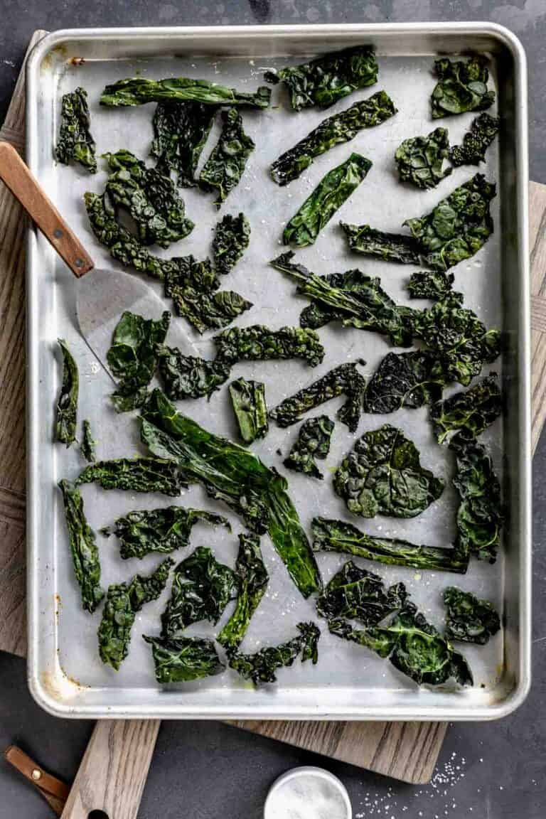 kale chips on a baking sheet with a small spatula