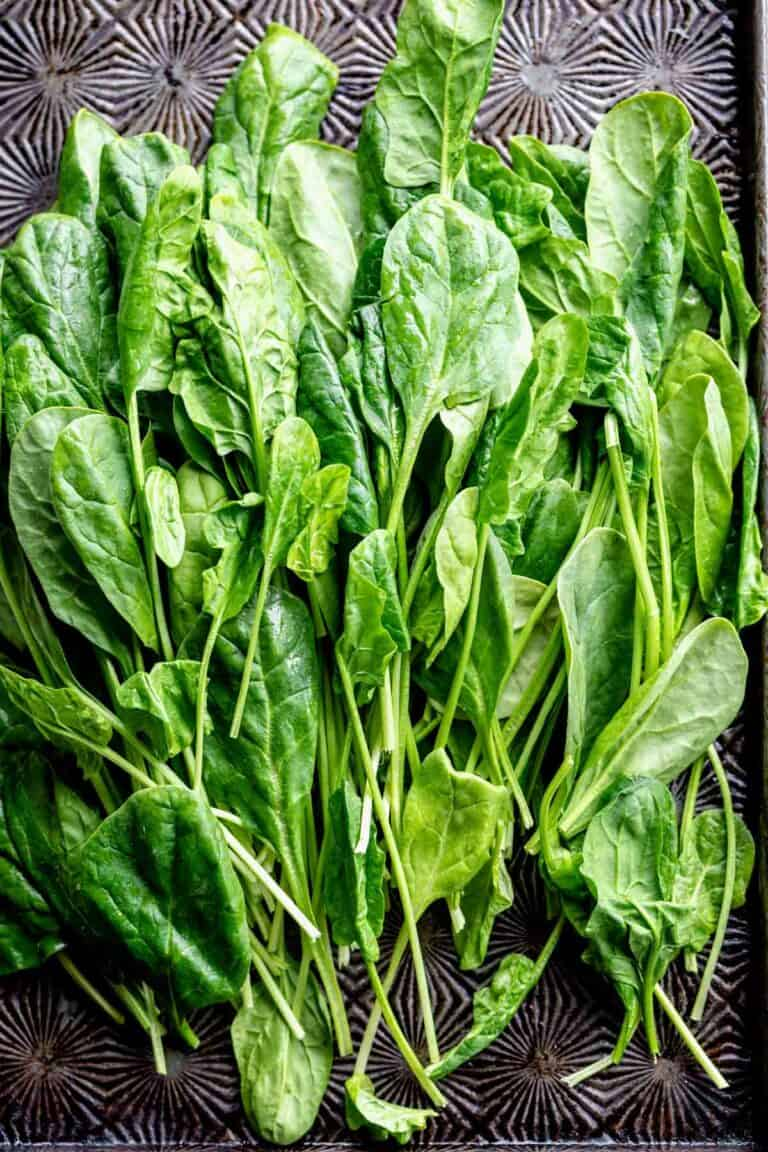 A bunch of spinach leaves on a dark table.