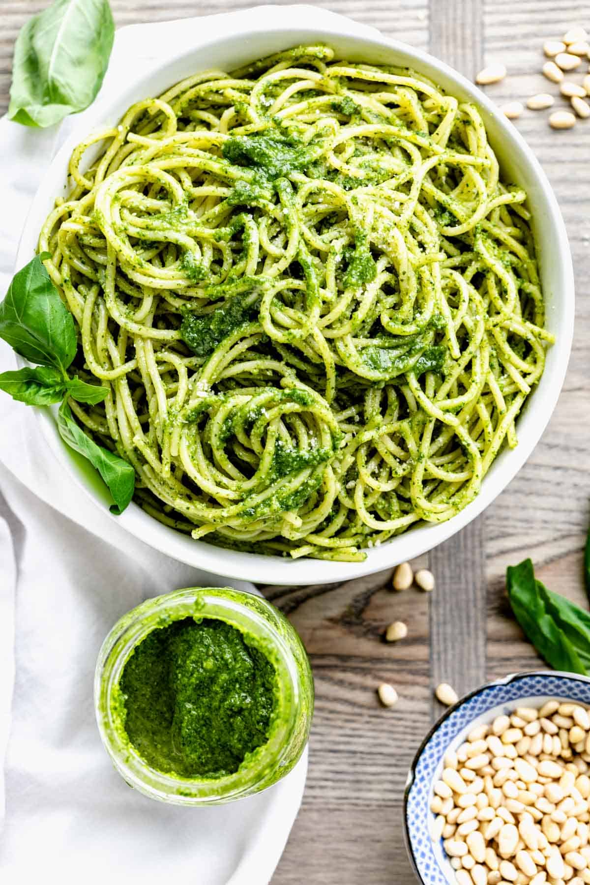 a bowl of pasta with pesto from overhead and a jar of pesto