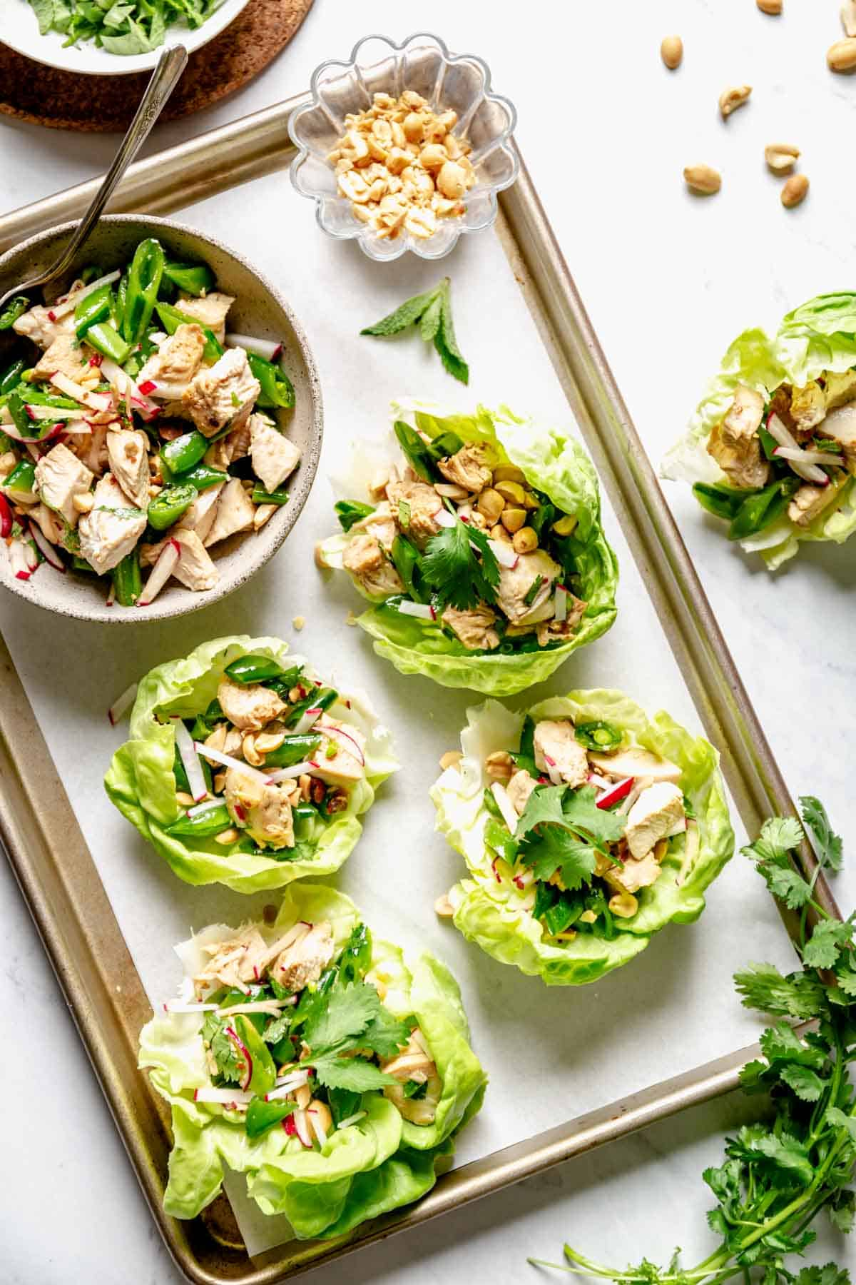 lettuce wraps being assembled on a sheet pan with peanuts
