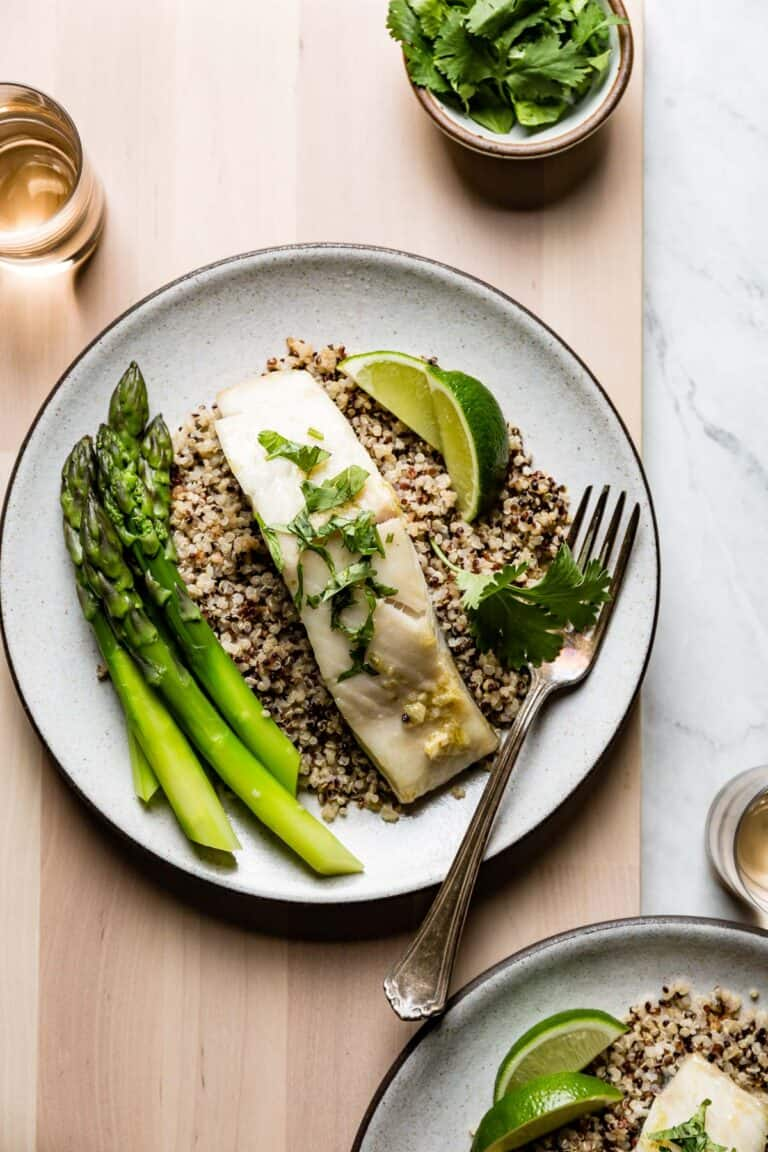 a plate of fish with asparagus and lime