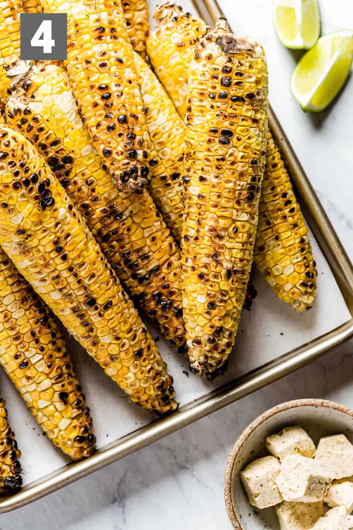 grilled corn with the flavored butter in a dish and lime wedges
