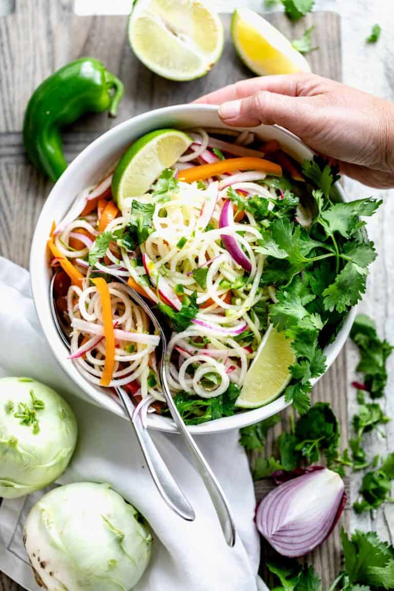 kohlrabi slaw with lime and cilantro in a bowl with a hand holding the bowl