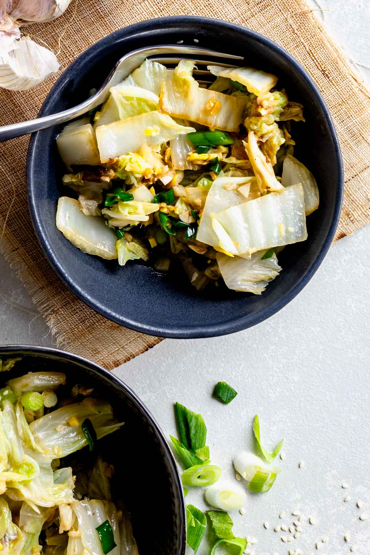 black bowls with stir-fried Napa cabbage in them