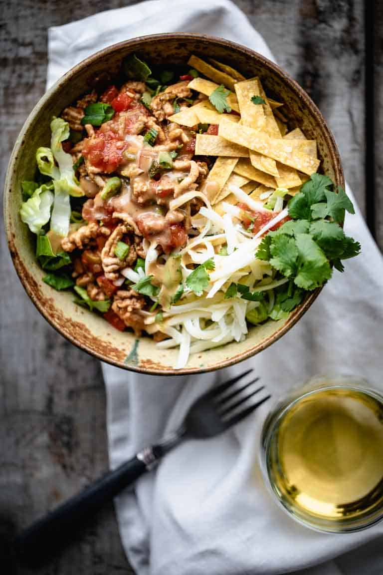 An overhead view of a serving of healthy taco salad with a glass of white wine