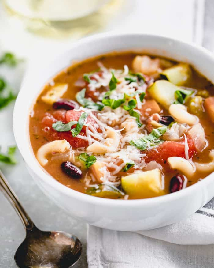 Classic minestrone soup in a white bowl on a white table with a kitchen cloth