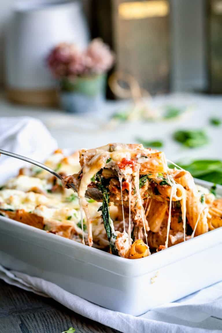 a scoop of cheesy pasta bake with cheese pull